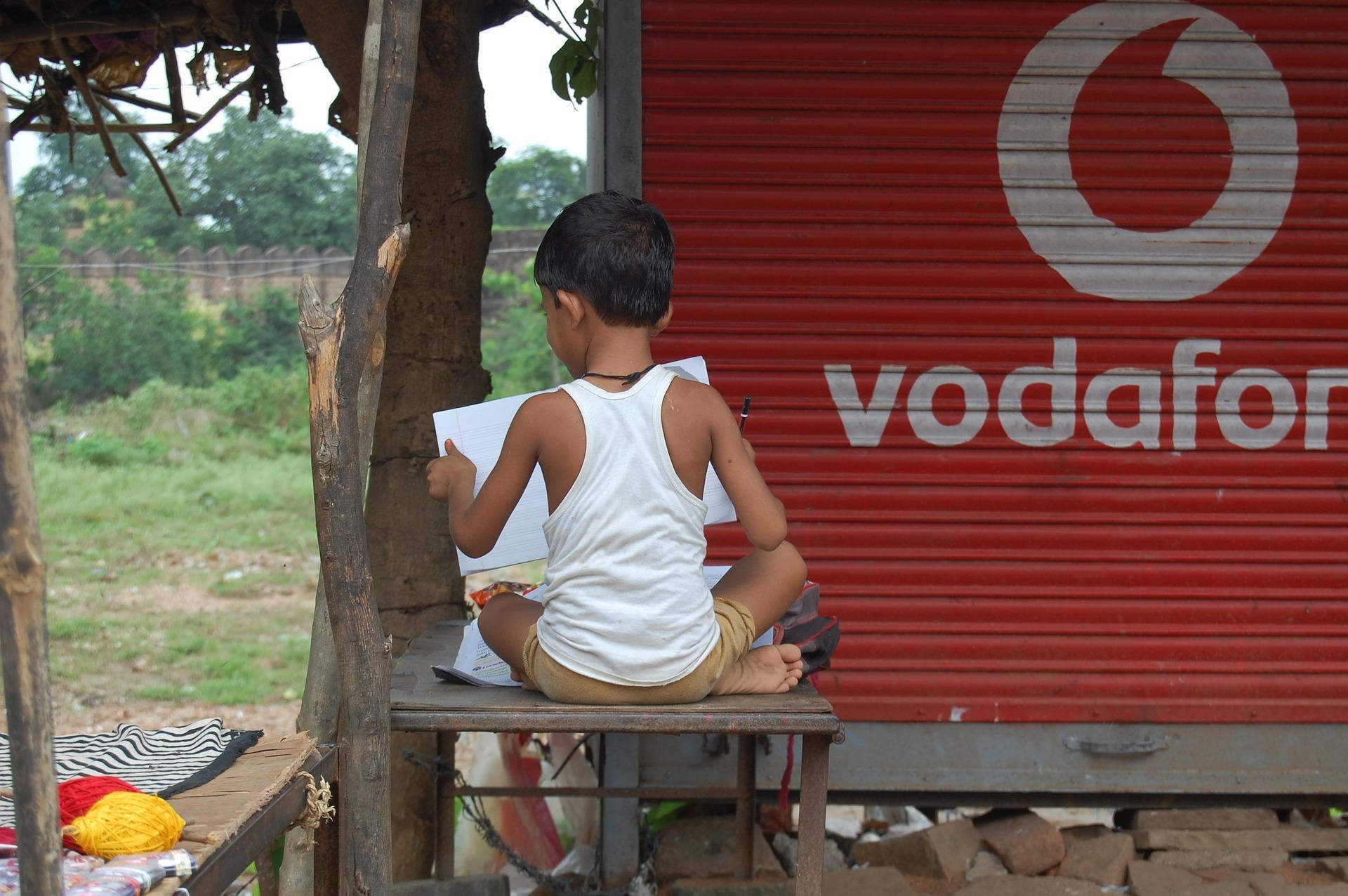 Indischer Junge vor Vodafone Signet