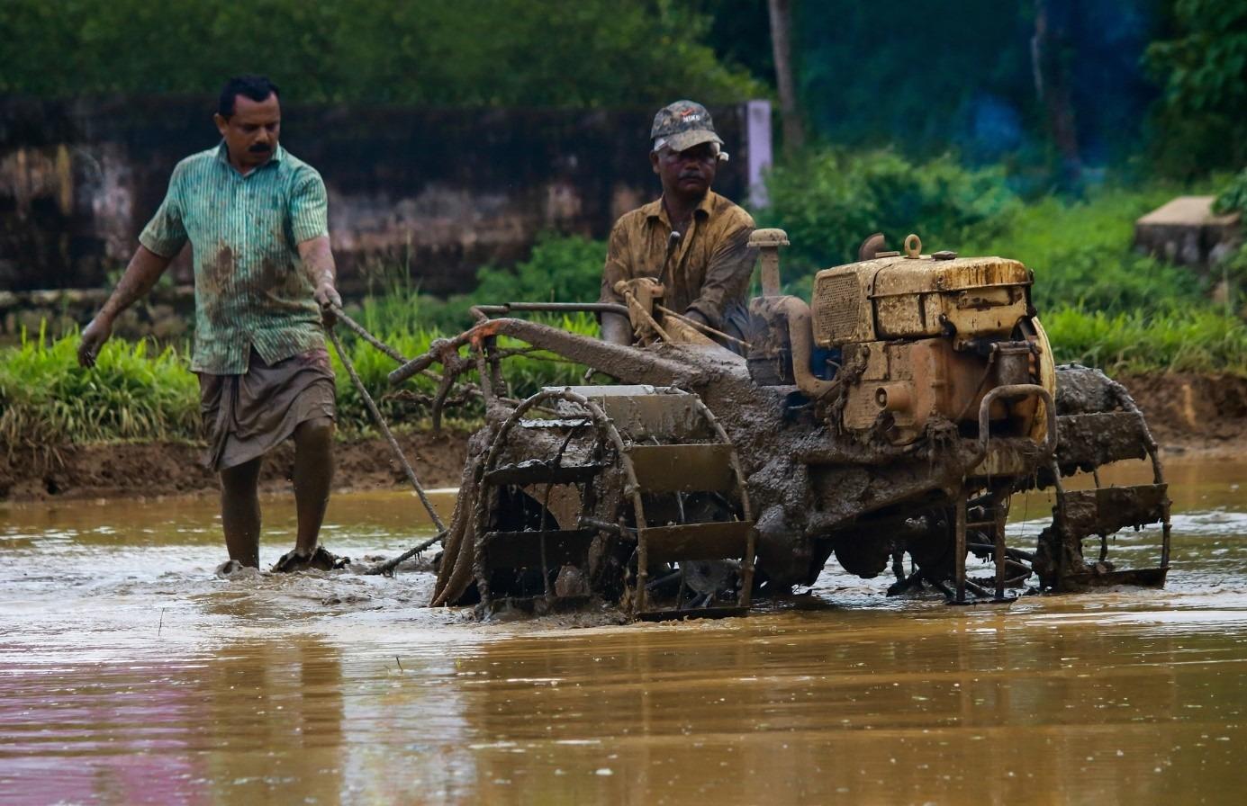 Indische Bauern bei der Landarbeit mit einer Zugmaschine